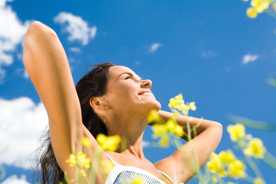 Blije vrouw met zwangerschapswens met blauwe lucht en bloemetjes