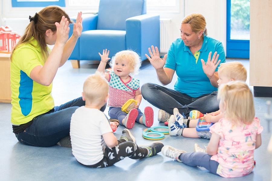 Vrolijke kindjes spelen samen met andere kinderen en begeleiders op kinderdagverblijf