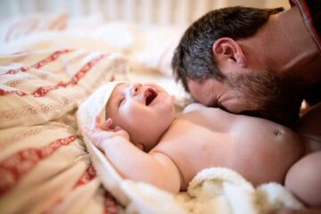 Vader blaast op buik van zijn baby