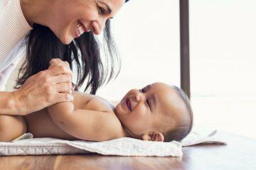 moeder lacht omdat haar baby zijn eerste babygeluidjes maakt