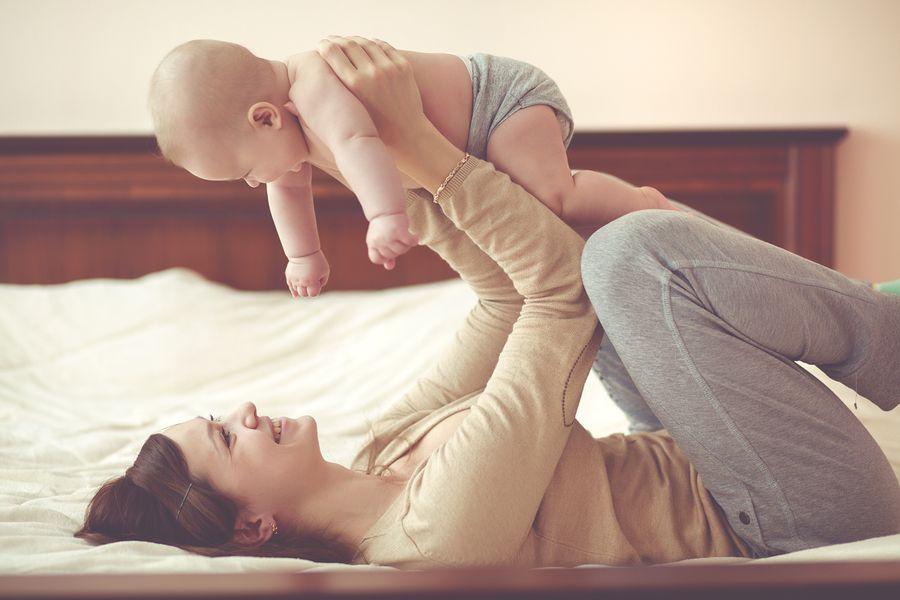Lachende moeder ligt op bed en tilt lachende baby van 19 weken oud op
