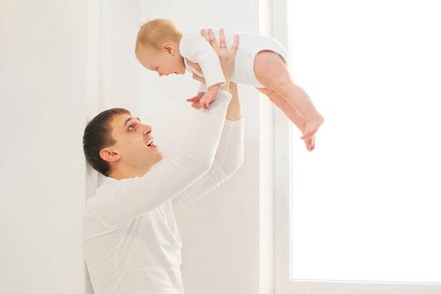 Vader-speelt-vliegtuigje-met-baby-van-19-weken-oud