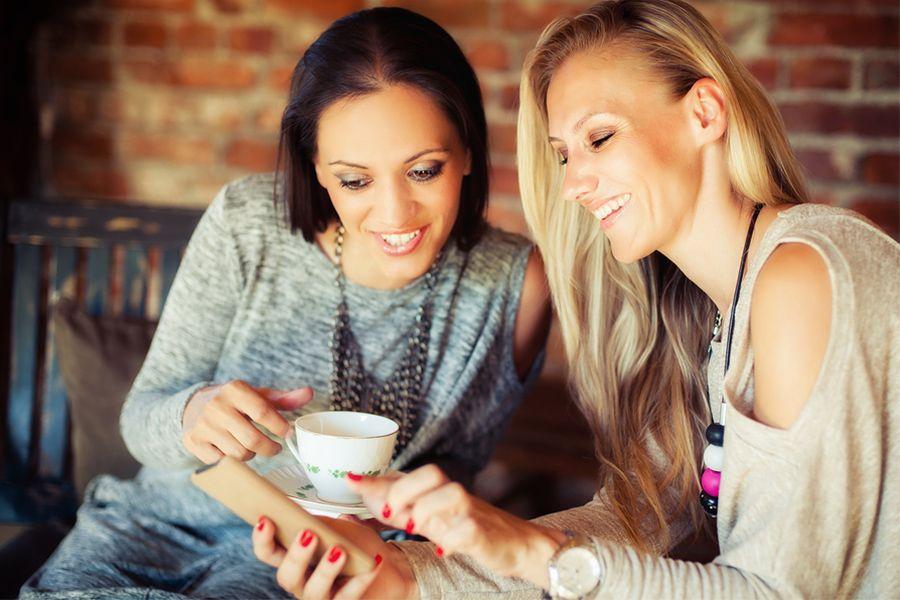Twee-jonge-vrouwen-in-cafe-drinken-koffie-en-lachen