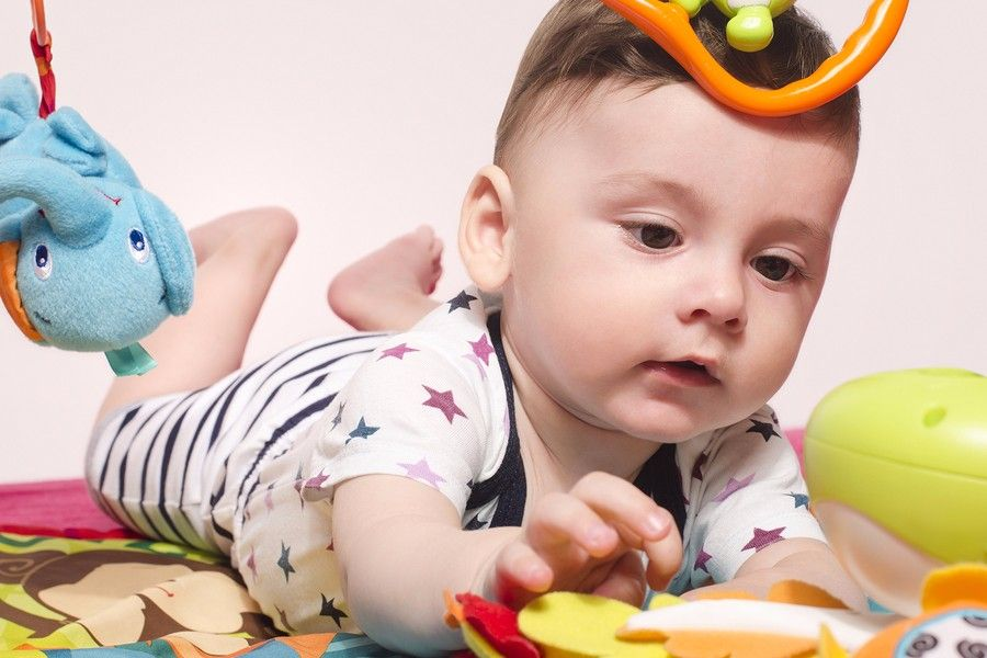 Baby van 23 weken oud ligt op zijn buik en grijpt naar speelgoed dat in de buurt ligt