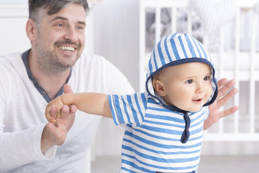 Vader houd baby van 25 weken oud vast bij handjes en baby fladdert met armpjes