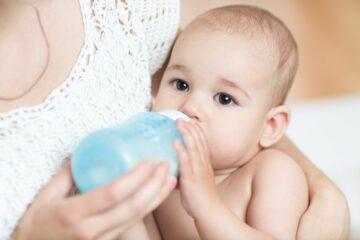 Moeder geeft baby met obstipatie fles