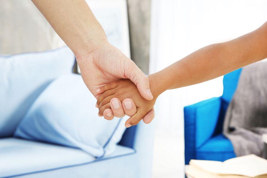 Blanke-volwassen-hand-houdt-donker-kinderhandje-vast-adoptie