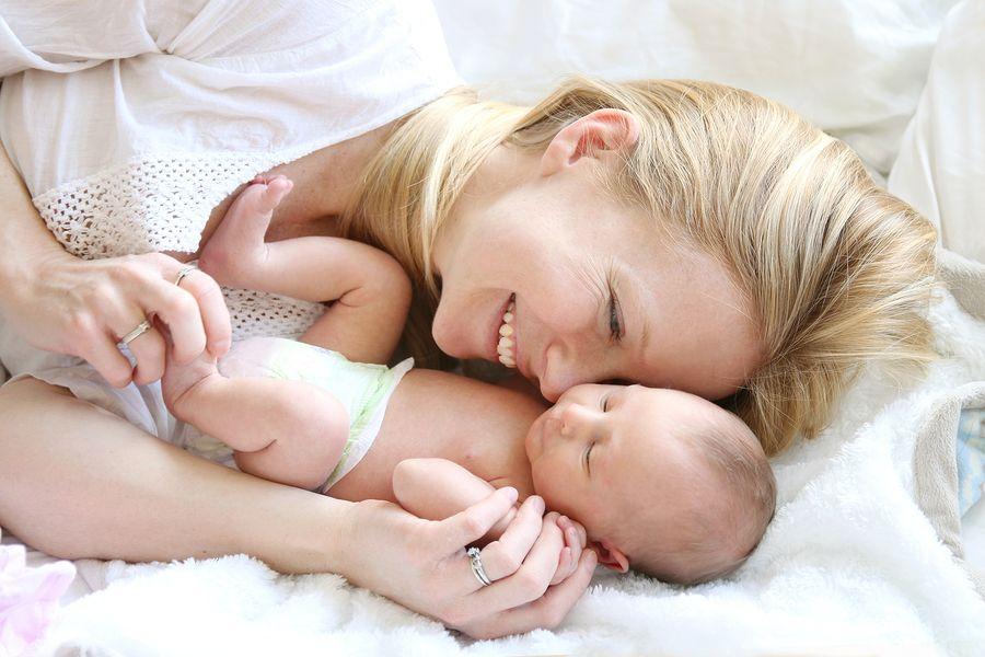 Moeder knuffelt met pasgeboren baby en is weer fit na de bevalling