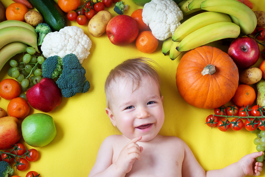 Baby van 4 maanden oud ligt tussen groente en fruit