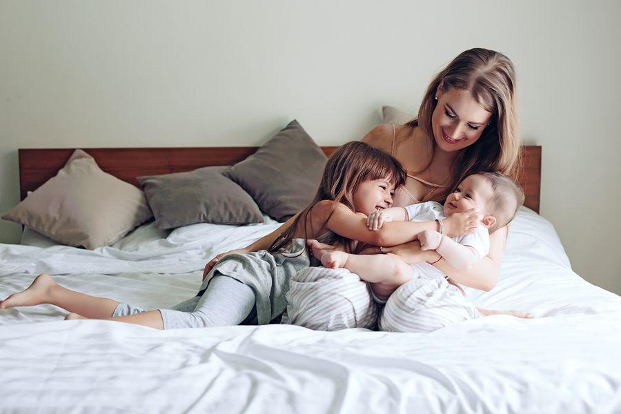 Moeder met 4 maanden oude baby en peuterkindje op bed