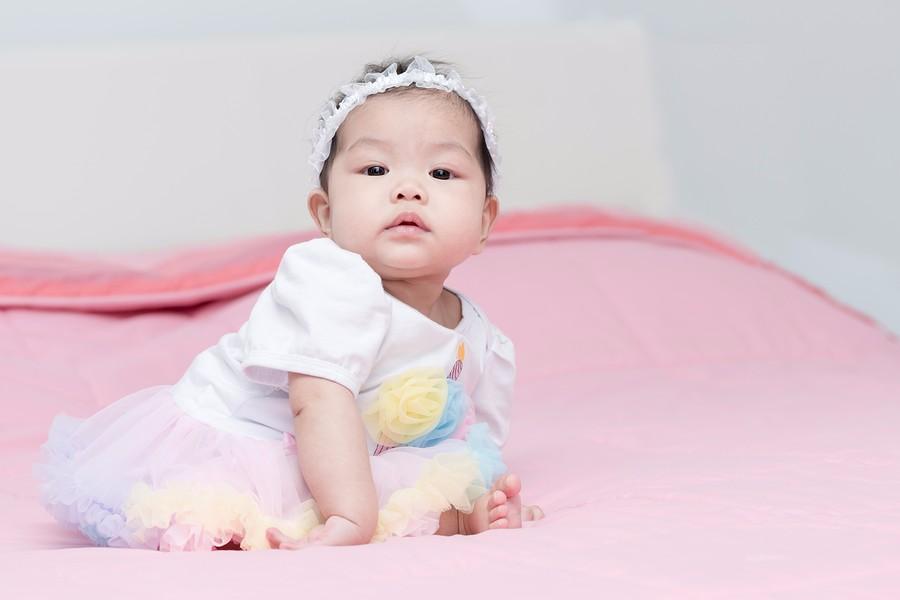 Aziatische baby van 6 maanden oud zit en leunt op haar armpje
