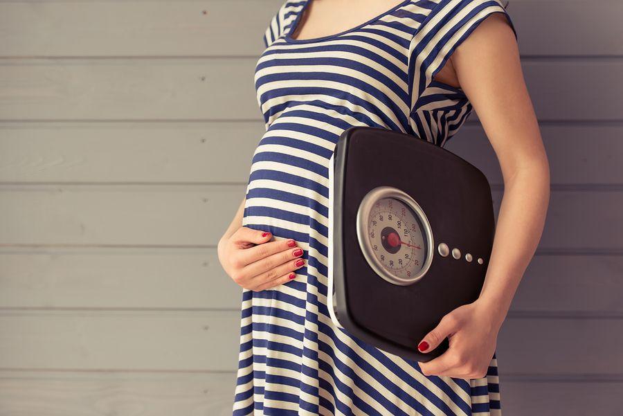 Vrouw met weegschaal die gezond wil afvallen tijdens zwangerschao