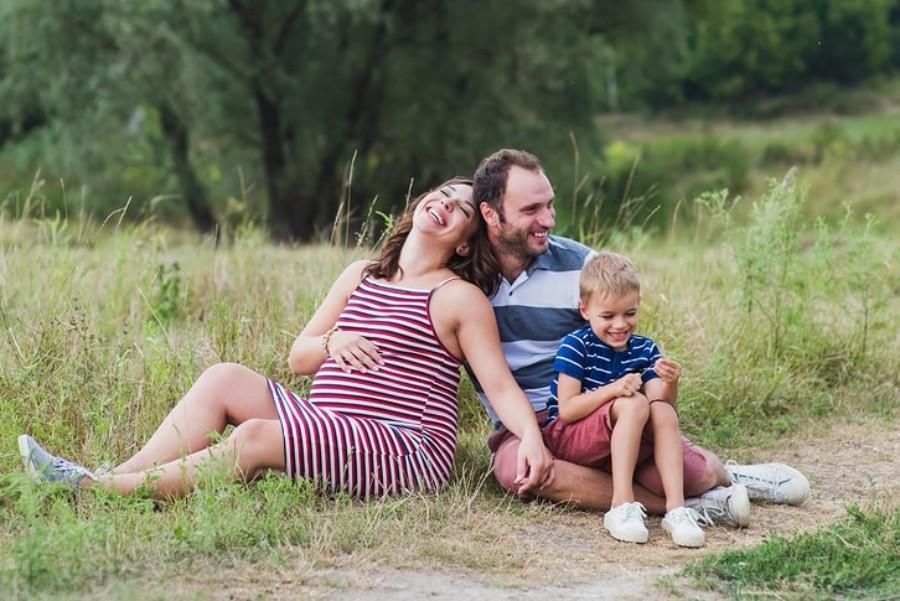 Zwangere vrouw zit lachend samen met gezin op grasveld