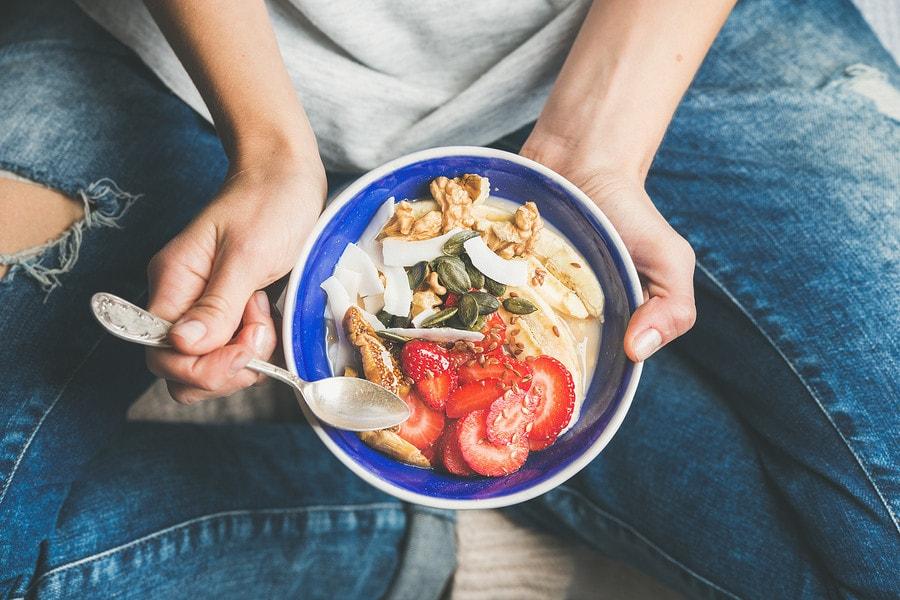Vrouw van 10 weken zwanger eet vezelrijk voedsel tegen obstipatie tijdens de zwangerschap