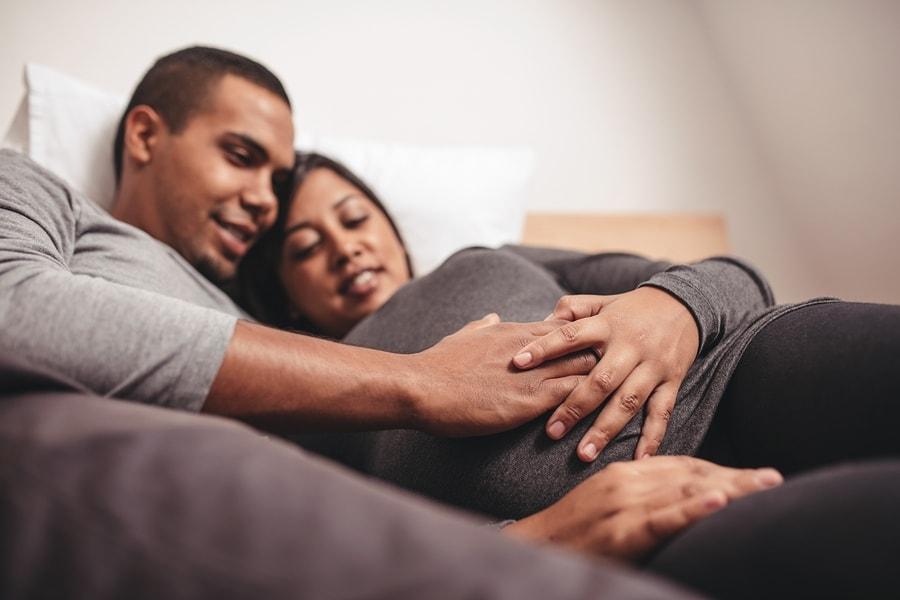 Man legt hand op buik van vrouw die 13 weken zwanger is