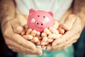 3 paar handen van een gezin houden samen een roze spaarvarken vast om de kosten van baby tot 12e jaar te illustreren