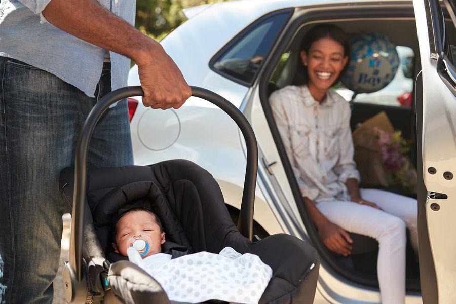 Vader tilt autostoeltje met pasgeboren baby uit auto