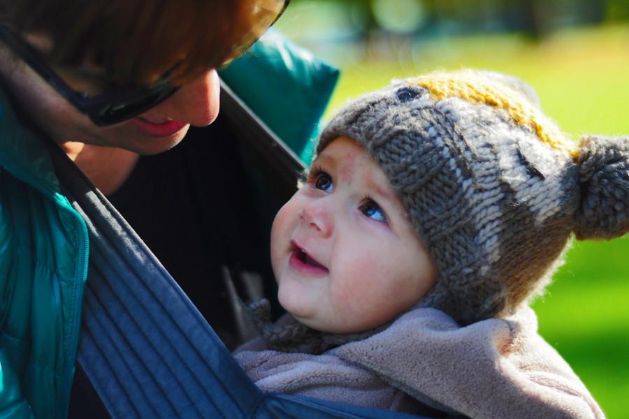 Baby van 12 maanden oud zegt bewust mama en kijkt moeder liefdevol aan