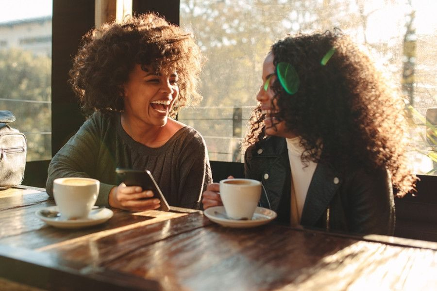 Twee vrouwen in café drinken koffie en lachen