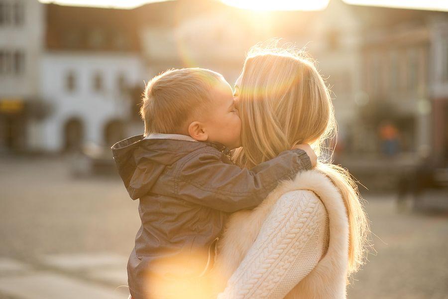Baby van 19 maanden oud geeft zijn moeder een kus, zij probeert hem goed op te voeden