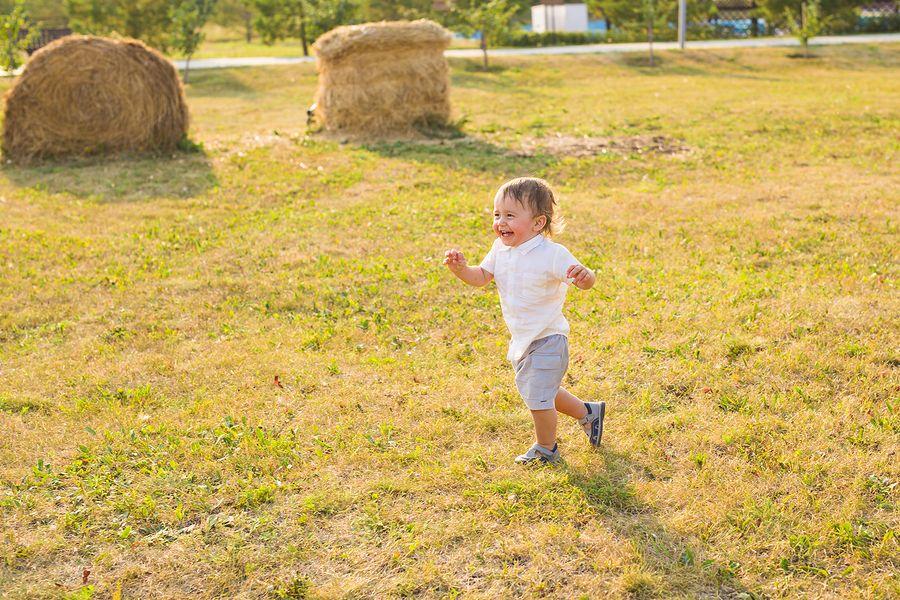Baby van 19 maanden oud rent over grasveld want hij speelt pakkertje