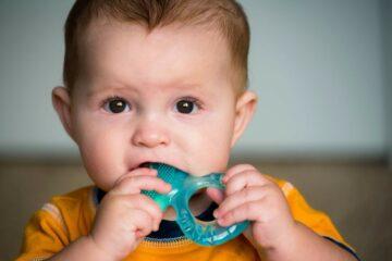 baby bijt op bijtring door eerste doorkomende tandjes