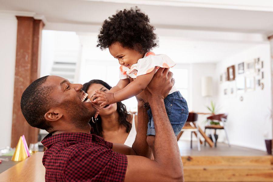 Vader tilt baby van 20 maanden oud op, ze lachen allebei