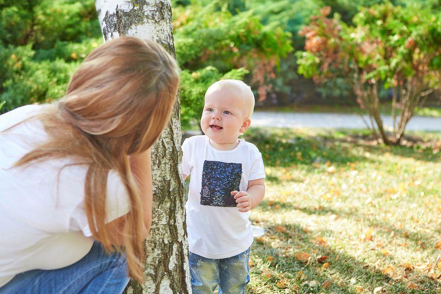Baby van 21 maanden oud speelt verstoppertje met zijn moeder