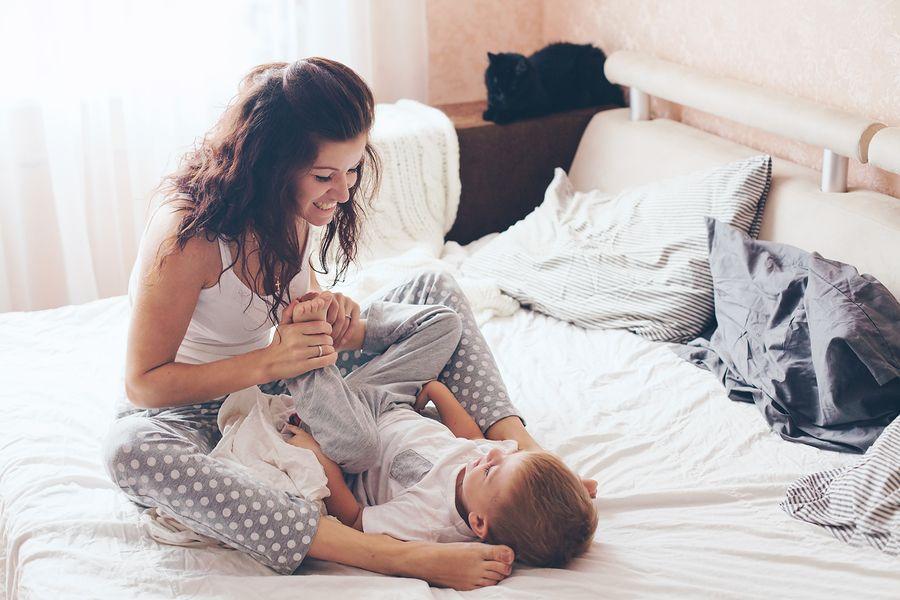 Moeder speelt op bed met baby van 22 maanden oud