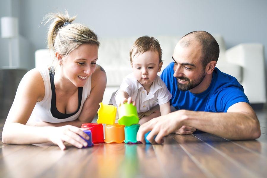 Vader, moeder en baby van 23 maanden oud bouwen samen een blokkentoren