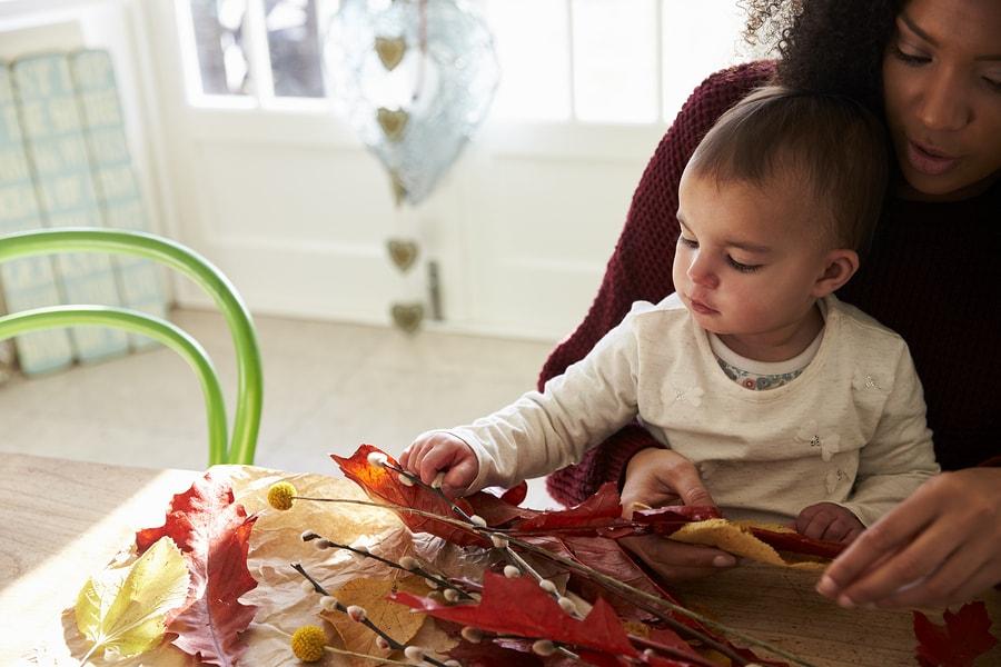 Moeder en baby van 24 maanden oud knutselen met bladeren en takken