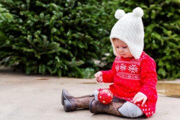 Baby heeft klassieke rode kersttrui aan als kerstkleding