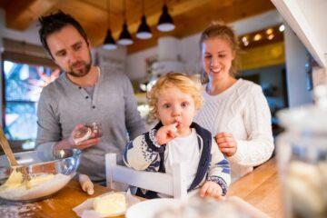 Vader, peuter en zwangere moedere maken samen zwangerschapsrecepten voor het kerstdiner klaar