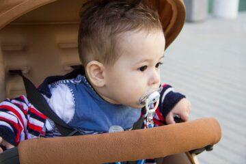 baby met speen in wandelwagen