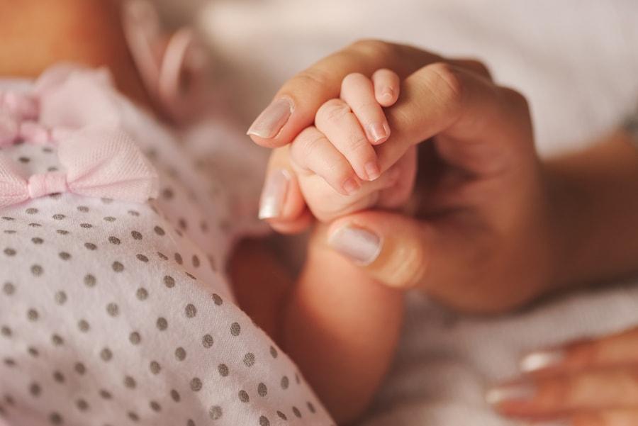Baby houdt hand moeder vast