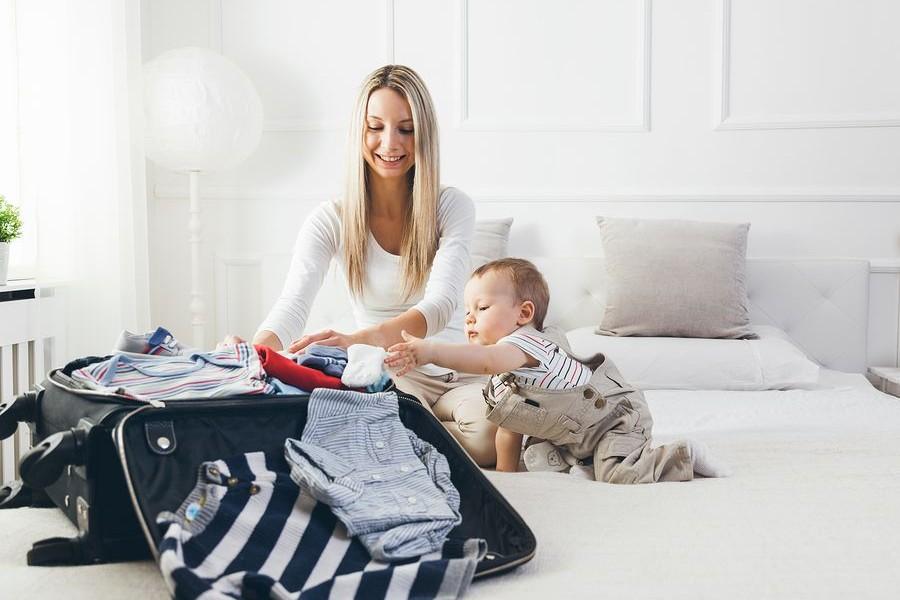Moeder en baby pakken koffer in voor vakantie