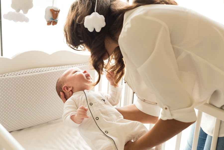 Moeder legt baby te slapen in ledikant