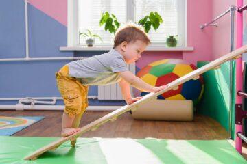 peuter doet aan peutergym en klimt op houten plank