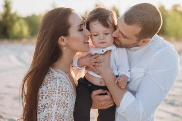 Moeder en vader knuffelen peuter en geven hem zelfvertrouwen