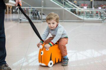 peuter op het vliegveld op reiskoffer
