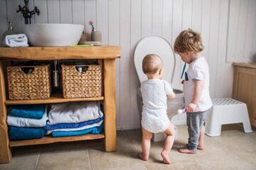 twee peuters staan bij de wc om broekplassen te voorkomen
