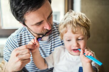 Vader is aan het tandepoetsen met peuter