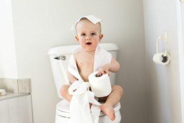 Kind speelt met wc-papier op de wc