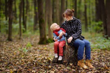 Moeder en peuter zijn aan het buitenspelen in de herfst