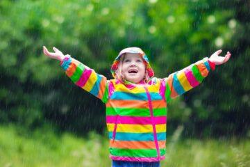 Meisje is aan het buitenspelen en danst in de regen