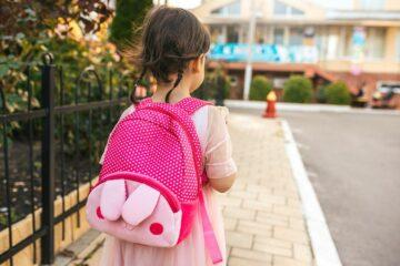 Meisje met rugzak gaat voor eerste schooldag naar school