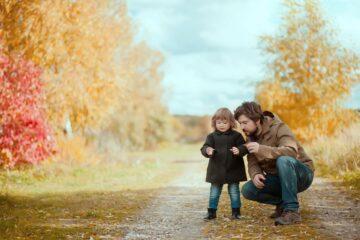 Vader en peuter zijn aan het buitenspelen en bekijken dieren