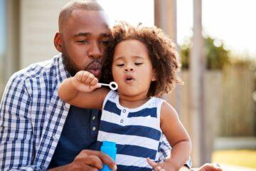 Vader blaast bellen met dochter: positieve aandacht in de opvoeding