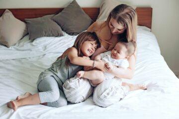 Moeder met haar eerste en tweede kind op bed, verdeelt de aandacht