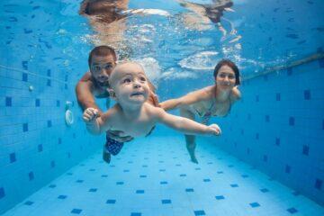 Ouders spelen in het zwembad met hun kind